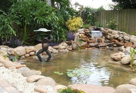 Симпатичный дачный водоем со скульптурой и водными растениями