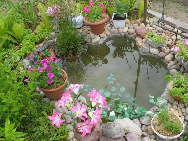 Миниатюрный дачный водоем с цветочными вазонами у бортика