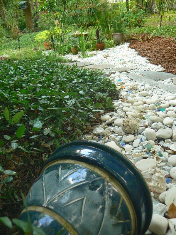 Сухой ручей из камней с кувшином придает саду нотку антикварности